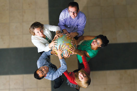 Students and Faculty holding the world in their hands.