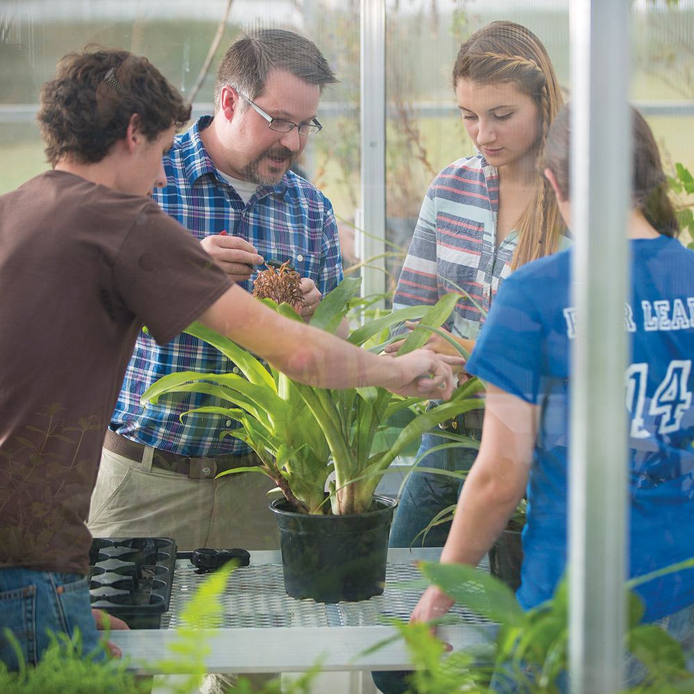 Norris Muth in Glaeser Greenhouse with students