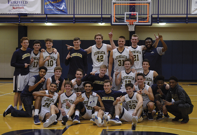 Basketball team poses with plaque