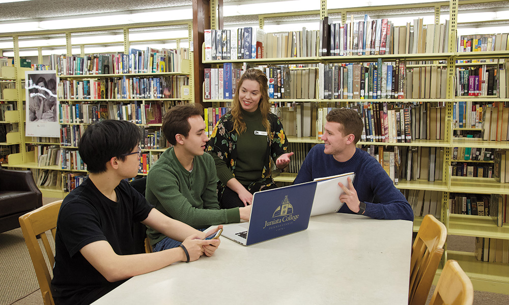 Autumn McDivitt of the Huntingdon County Library, 				standing, met with members of the I4I team, from the left, 				Jin'ao Zhu '20 of Wen Ling, Tai Zhou, China, Tyler Paul '21 				of Johnstown, Pa., and Hudson Speck '20 of Huntingdon, to 				review plans for a memory lab to preserve local history.
