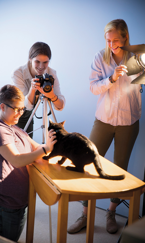 Integrated Media Arts (IMA) students, 				from the left, Ace Simek '21 of Arlington, 				Va., Genevieve Wittrock '22 of 				Collegeville, Pa., and Tatum Poirier '21 				of Evans City, Pa., work to capture a 				portrait of Flynn, an adoptable cat at the 				Huntingdon County Humane Society.