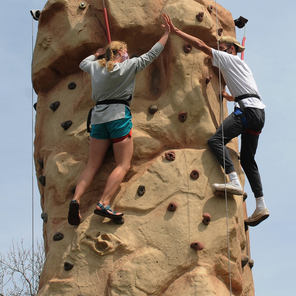 Students climb a rock wall