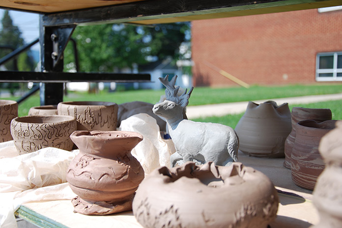 pottery pieces drying on racks