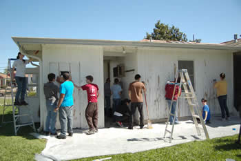 Students painting a house