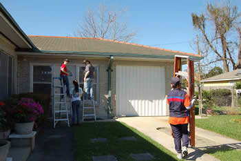 Students finishing painting a house
